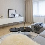 minimalistická obývačka so sivou rohovou sedačkou, lesklými stolíkmi a závesným TV bielym stolíkom