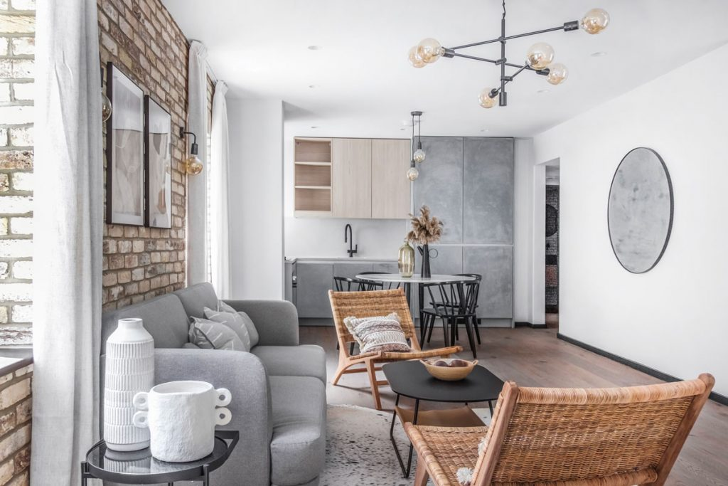 prírodný interiér obývačky a kuchyne, so sivou pohovkou, prírodnými kreslami, tehlovou stenou, kuchynskou linkou s betónovou stierkou a v kombinácii farieb sivej, bielej, čiernej a hnedej