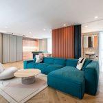 otvorený interiér apartmánu, v ktorom je obývačka spojená s kuchyňou a kúpeľňou, materiály terazzo, drevené obklady a pastelové farby