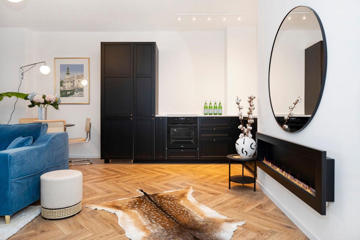 otvorený priestor obývačky a kuchyne s modrou sedačkou, čiernou kuchynskou linkou, jedálenským kútom a biokrbom
