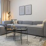 minimalistická obývačka s modulárnou sivou sedačkou a čiernym konferenčným stolíkom