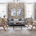 Prírodný interiér obývačky s tehlovou stenou, sivou sedačkou, kreslami, neutrálnym sivým kobercom a čiernym lesklým stolíkom