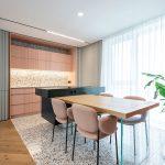 kuchyňa s terazzom na podlahe a kuchynskej zástene, s kuchynskou linkou v pastelovej lososovej, s čiernym kuchynským ostrovčekom, z ktorého vychádza jedálenský stôl podopretý sklenenou podnožou