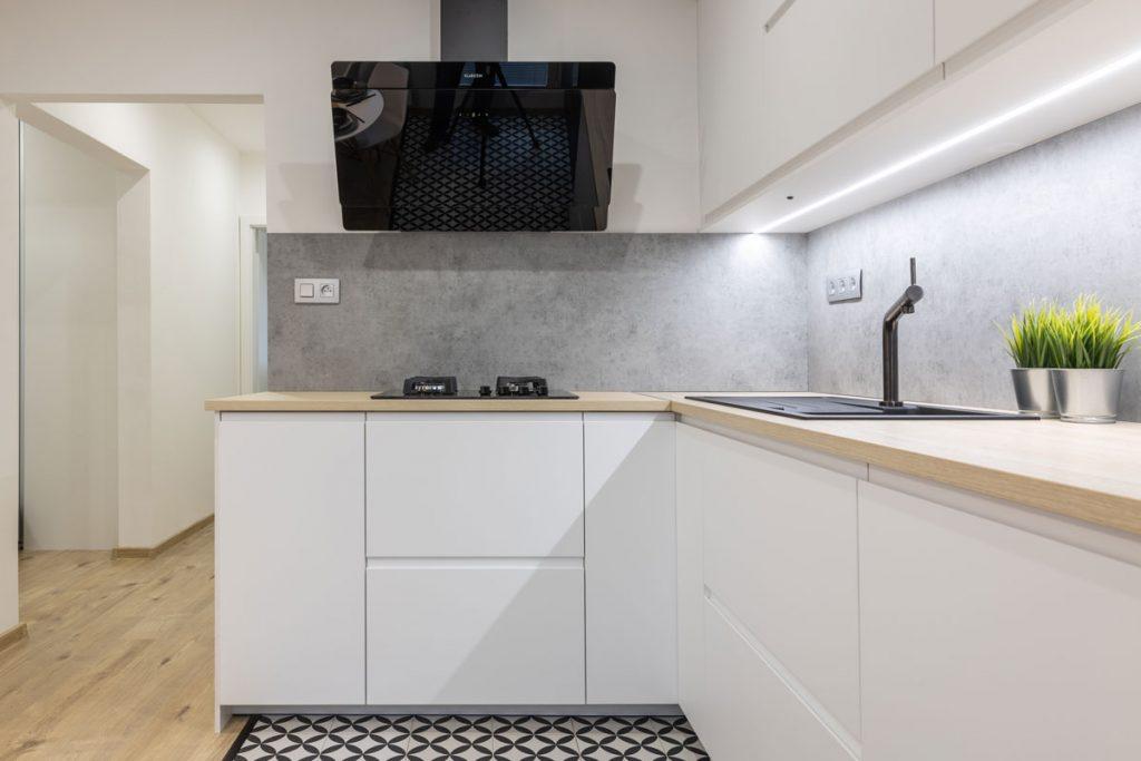 kuchynská rohová linka v bielej farbe so zástenou so vzhľadom betónu