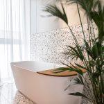 Kúpeľňa s terazzo obkladom a jednoduchou bielou samostatne stojacou vaňou