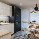 kuchyňa s rohovou kuchynskou linkou, vstavanými spotrebičmi v čiernej skrini a geometrickou čiernou-bielou podlahou