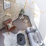 asymetrický priestor bytu so sivou sedačkou, koženým kreslom, čiernym stolíkom a zvieracou kožou