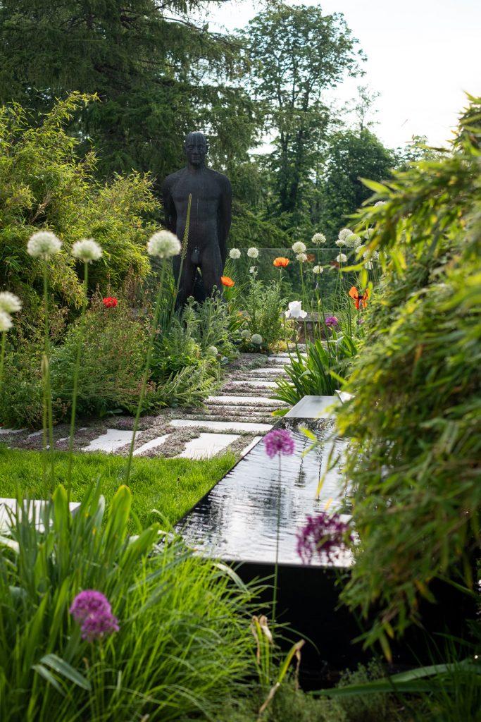 menšia okrasná záhrada so sochou od umeleckého sochára, s bambusmi, okrasnými trávami, okrasnými cesnakmi, vodným prvkom a vápencovými nášľapnými kameňmi