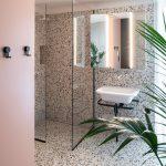 Kúpeľňa s terazzo obkladom, štvorcovým podsvieteným zrkadlom a sprchovacím kútom