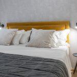 spálňa v šedých farbách s horčicovožltou posteľou