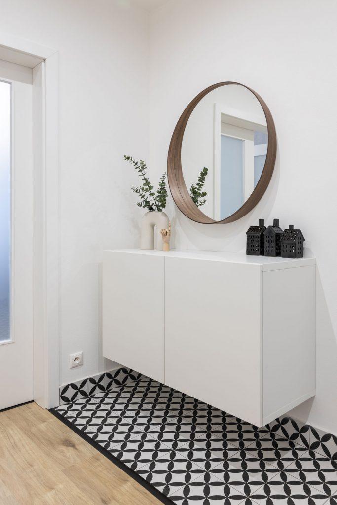 kúpeľňa s minimalistickou závesnou bielou skrinkou, okrúhlym zrkadlom a čierno-bielou dlažbou s geometrickým vzorom