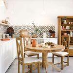 Kuchyňa s bielou kuchynskou linkou, masívnym jedálenským stolom a vitrínou