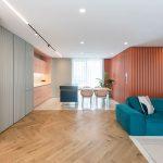 Otvorený priestor obývačky a kuchyne s drevenými oblými lamelovými obkladmi, terazzom a pastelovými farbami