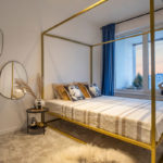 extravagantná spálňa so zlatou posteľou, zrkadlami nepravidelného oválneho tvaru a modrými závesmi