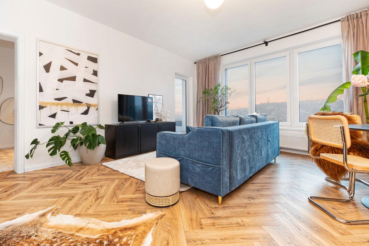 obývačka s modrou sedačkou, abstraktným obrazom, zelenými kvetmi, kožušinou na zemi a jedálenským stolom