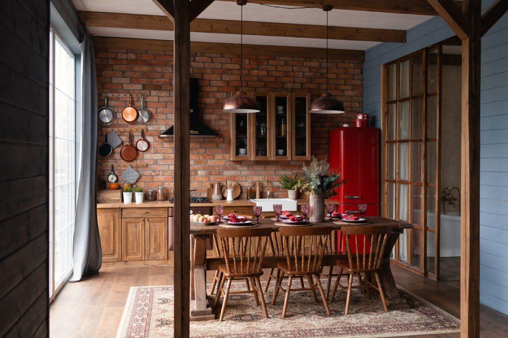 Vidiecka kuchyňa s tehlovou stenou a priznanými trámami