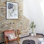 Prírodne ladený interiér s koženým kreslom, zvieracou kožou na podlahe a tehlovým obkladom stien