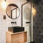 kontrastná čierno-biela kúpeľňa s antracitovým geometrickým obkladom v sprchovacom boxe, bielym obkladom, čiernym umývadlom a drevenou umývadlovou skrinkou