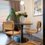 jedálenský kút s čiernym okrúhlym stolom, ratanovými stoličkami s kovovými nohami a obrazom v zlatom ráme