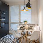 minimalistická rohová kuchynská linka v bielej farbe, podlaha s čierno-bielym geometrickým vzorom a jedálenský stôl v bielej farbe v kombinácii s drevom