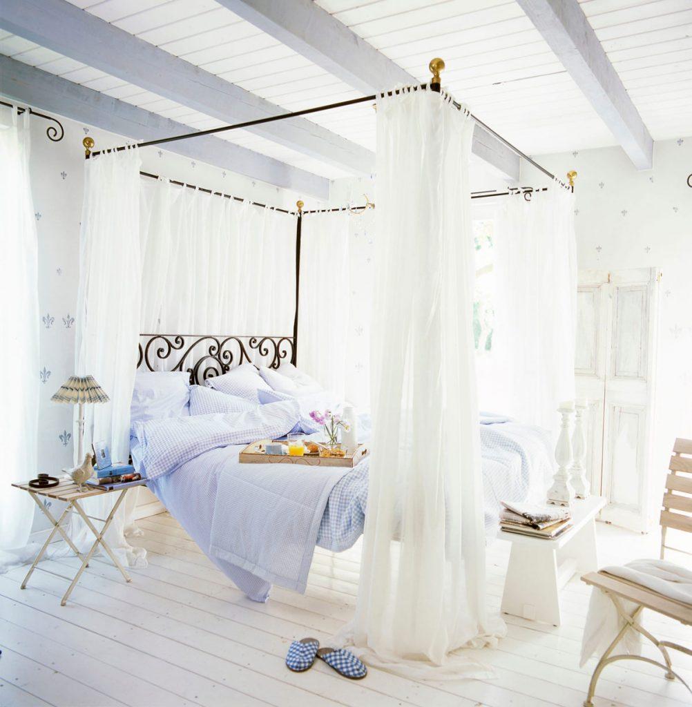vidiecka spálňa s modrými posteľnými obliečkami a nebesami nad posteľou