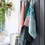 Vešiak na uteráky s motívom opíc pripevnený na kúpeľňové dvere