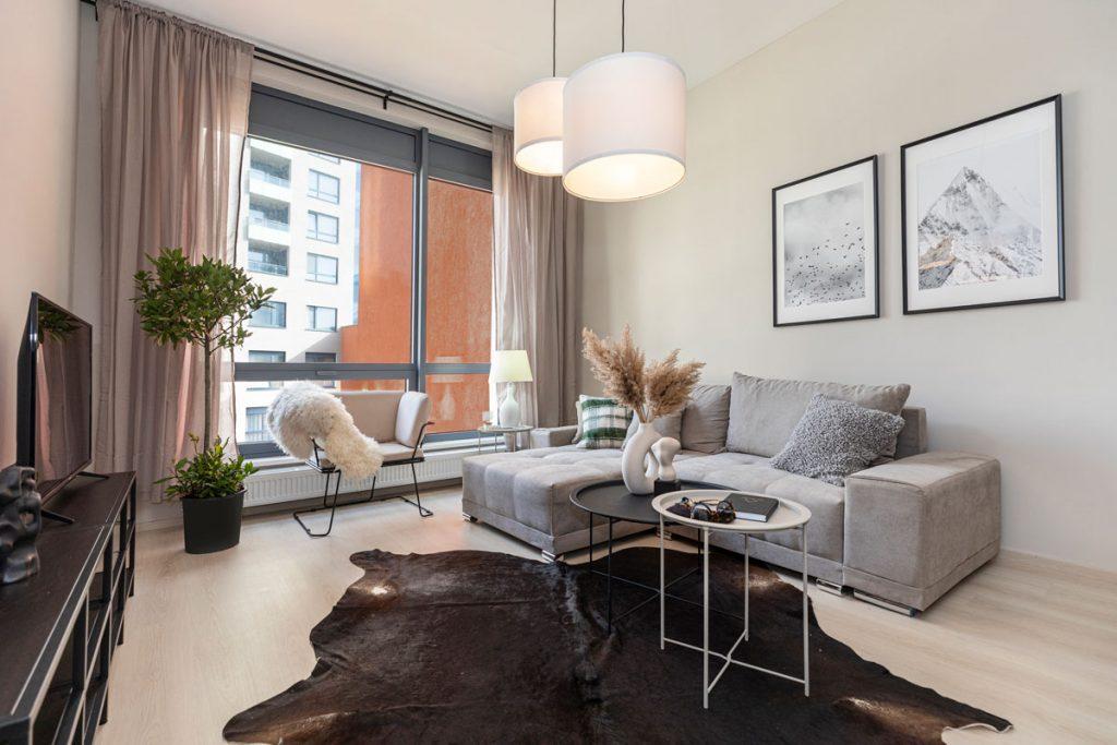 obývačka v novostavbe so sivou sedačkou a smotanovým kreslom, hnedou kožušinou, čiernou TV skrinkou a kovovými konferenčnými stolíkmi