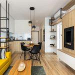 Industriálny dvojizbový byt: obývačka spojená s kuchyňou zariadená drevom, kovovými prvkami a žltou sedačkou