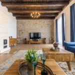 Obývačka s modrou sedačkou, retro masívnym stolíkom, so starožitnými dekoráciami, dobovými kusmi nábytku, tkaným kobercom, bielou kachľovou pecou a priznanou kamennou stenou