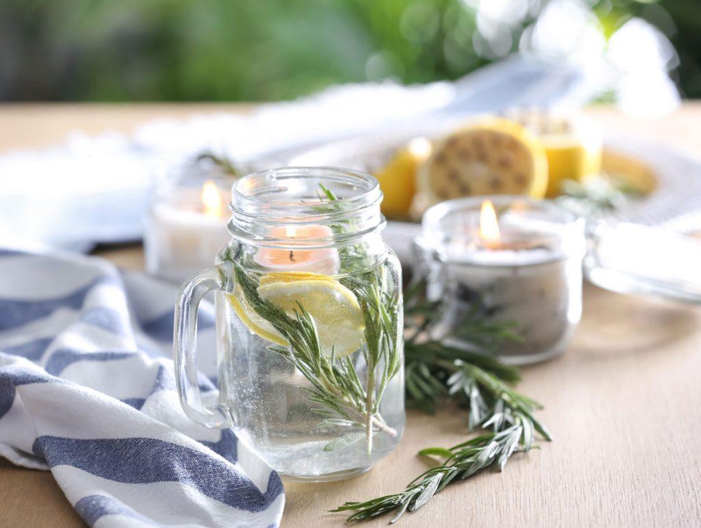 Pohár s vodou, citrónom, rozmarínom, sviečkou a éterickými olejmi ako repelent proti hmyzu