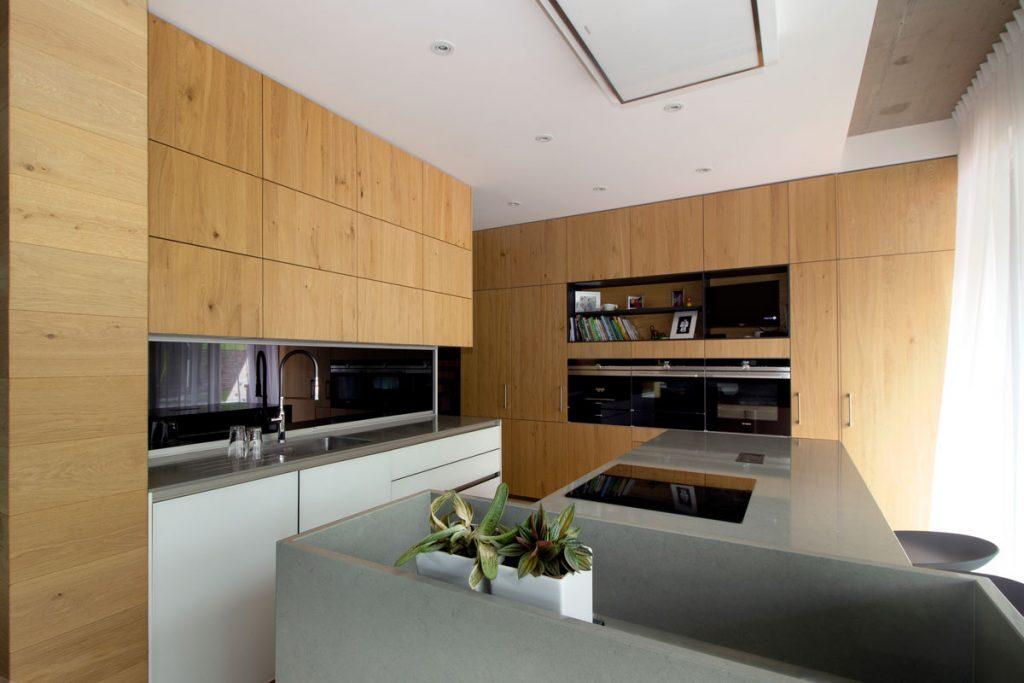 moderná kuchyňa z dubovej dyhy, s výsuvnou zástenou na uskladnenie kuchynských spotrebičov a tajným vstupom do komory vedľa zabudovanej chladničky