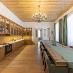 kuchyňa s rohovou kuchynskou linkou vyrobenou na mieru a jedálenský stolom pre dvanásť ľudí zhotoveným zo starých trámov