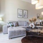 obývačka prepojená s kuchyňou: sivá sedačka, konferenčné stolíky, kožušina na podlahe, jedálenský kút a biely kuchynská linka