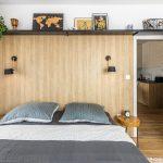 Spálňa s dekorom bieleného duba a neutrálnymi textíliami na posteli