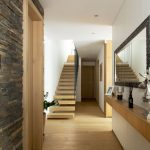chodba v rodinnom dome so závesnou skrinkou, zrkadlom a minimalisticky riešeným schodiskom