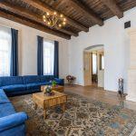 obývačka s modrou rohovou sedačkou, tkaným orientálnym kobercom, starožitnými stolíkmi a šamotovými kachľami