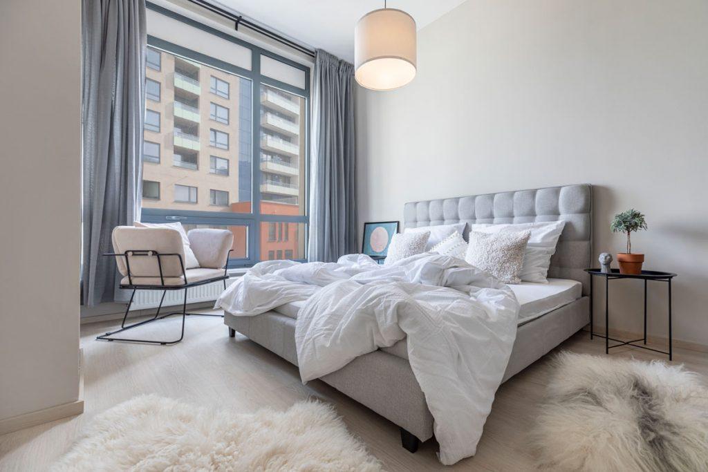 spálňa so sivou čalúnenou posteľou, ovčími kožušinami, smotanovým kreslom a veľkým oknom od podlahy po strop