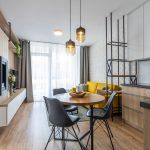 Industriálny interiér obývačky spojenej s kuchyňou, so žltou sedačkou, kovovým regálom, drevenou kuchynskou linkou a jedálenským stolom s čiernymi stoličkami