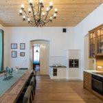 kuchyňa s kuchynskou linkou z dreva a jedálenským stolom vyrobeným z trámov pre 12 ľudí