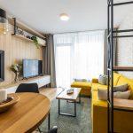 interiér obývačky spojenej s kuchyňou, so žltou sedačkou, TV stenou s dubovým obkladom a zabudovaným biokrbom