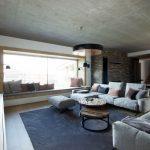 moderná obývačka so sivou sedačkou, okrúhlymi drevenými stolíkmi, veľkorysou nikou so sedením a podhľadovým betónovým stropom
