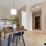 biela kuchynská linka a jedálenský kút s masívnym dreveným stolom a čalúnenými stoličkami