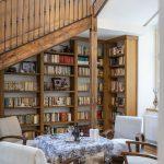 monumentálne schodisko v storočnom dome, pod ktorým je drevená knižnica a priestor so stolom a kreslami