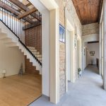 chodba v historickom rodinnom sídle s priznaným kameňom a tehlou na stenách a keramickou podlahou v dekóre betónu