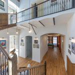 otvorený priestor centrálnej chodby v dome so schodiskom, vstupom do sauny či miestnosti s biliardovým stolom