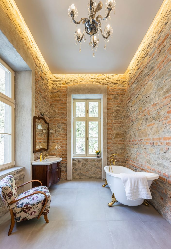 kúpeľňa s priznanými kamennými a tehlovými stenami, podsvieteným stropom, bielou vaňou na zlatých nožičkách, kvetinovým kreslom a starožitnou skrinkou s umývadlom