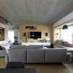 """moderná obývačka s """"kukaňou"""" v podobe veľkej niky na sedenie, sivou sedacou súpravou, TV stenou susediacou s posilňovňou, podhľadovým betónom a knižnicou vo výklenku"""