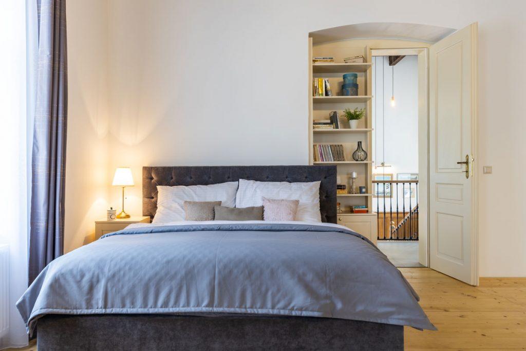 klasická spálňa s čalúnenou posteľou a modrými obliečkami a dverami so vstavanou knižnicou