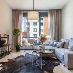 obývačka v novostavbe zariadená v neutrálnych farbách: sivá sedačka, hnedá zvieracia koža, biely a čierny kovový konferenčný stolík a smotanové dizajnové kreslo