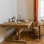 kútik na čítanie s čalúneným retro kreslom a masívnym dreveným stolom